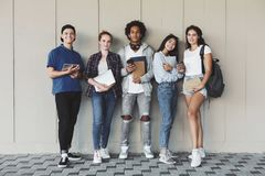 Happy college students posing with studying staff at campus wall royalty free stock image
