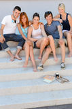Happy college students sitting on stairs summer. Full length of happy college students sitting together on campus  stairs Royalty Free Stock Image