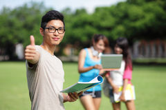 Happy College students. Happy College student men smile and show thumb up to you on campus lawn, asian Stock Image
