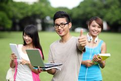 Happy College students. Happy College student men smile and show thumb up to you on campus lawn, asian Stock Photo