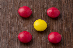 Happy colorful chocolate balls on wooden background Royalty Free Stock Photos