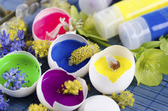 Happy colorful Easter decoration with egg shells filled with paints and spring flowers. On blue pad royalty free stock photo