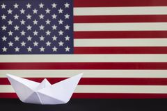 Happy Columbus Day, the great National USA holiday. Celebrated on the second Monday in October. White paper boat over blurred Amer. Ican flag. Stripes and stars royalty free stock image