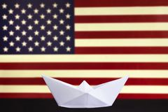 Happy Columbus Day, the great National USA holiday. Celebrated on the second Monday in October. White paper boat over blurred Amer. Ican flag. Stripes and stars royalty free illustration