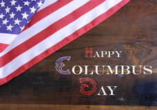 Happy Columbus Day greeting message text on dark rustic recycled wood. Background with USA stars and stripes flag Stock Image