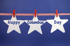 Happy Columbus Day message greeting written across white star cards hanging from red stripes ribbon and pegs on a line. Against a patriotic blue background for stock photography