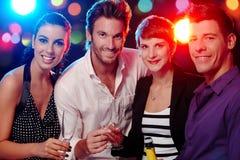 Happy companionship in discotheque. Happy companionship drinking, smiling in discotheque Royalty Free Stock Photos