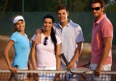 Happy companionship on tennis court. Happy companionship standing on tennis court, smiling royalty free stock photos