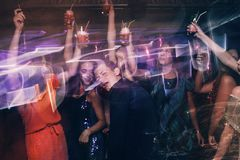 Happy company on dance floor. Joyful New Year in night club, active Christmas celebration in motion. Disco party in blurred colors, modern youth life, pickup Royalty Free Stock Images