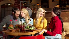 Pretty girls and cheerful boy sitting together at table and are eating burgers. Happy company eating tasty fast food in cafe. Pretty girls and cheerful boy stock video