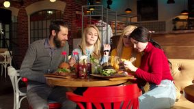 Happy company taking selfie while eating tasty fast food in cafe. Pretty girls and cheerful boy sitting together at table and are eating burgers. Concept of stock video