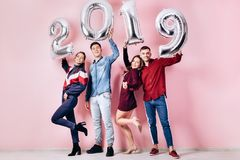 Happy company of two girls and two guys dressed in stylish clothes are holding balloons in the shape of numbers 2019 stock photo