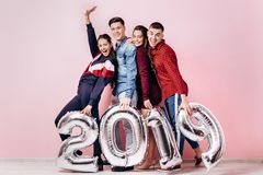 Happy company of two girls and two guys dressed in stylish clothes are holding balloons in the shape of numbers 2019 on stock photo