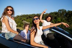 Happy company of young women and guys are sitting in a black convertible car on the country road on a sunny day. royalty free stock image