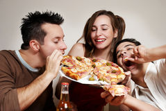 Happy company of youth eating a pizza Royalty Free Stock Photo