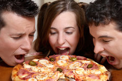 Happy company of youth eating a pizza Royalty Free Stock Images