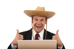 Happy computer man with thumbs up. Caucasian business man in suit and tie with a straw hat and big smile gives thumbs up from behind a shiny silver laptop Royalty Free Stock Photo