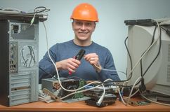 Computer repairman. Computer technician engineer. Support service. Happy Computer network technician is crimping a network cable by crimper tool in his hands royalty free stock image