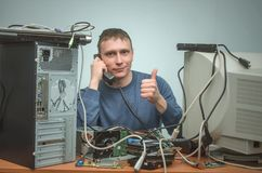 Computer repairman. Computer technician engineer. Support service. Happy Computer technician is consulting a users by the phone and showing a thumbs up. PC Royalty Free Stock Images
