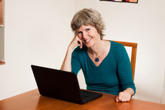 Happy computer user. Mature lady, smiling warmly after a positive internet experience. Possibly after a Photo upload, communicating with friends and family Stock Images