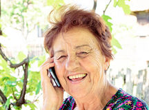 Happy comunnication. Old lady using mobile phone and have smile on her face Stock Photos
