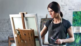 Happy concentrated beautiful female painter enjoying drawing picture in art studio medium shot stock footage