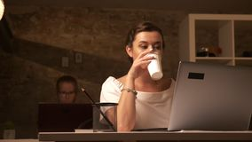 Happy concentrated caucasian female is drinking coffee and looking at computer while sitting next to her associate on. Brick background stock video footage