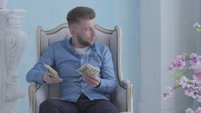 Happy rich bearded man in blue shirt sitting in the white armchair in the light room counting money. Young businessman. Happy concentrated rich bearded man in stock footage