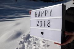 Happy 2008 concept. Slogan `happy 2018` held by a woman in a snowy landscape Royalty Free Stock Images