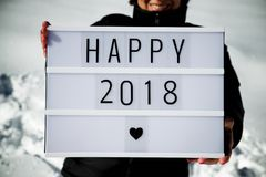 Happy 2008 concept. Slogan `happy 2018` held by a woman in a snowy landscape Stock Image