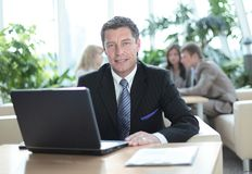 Happy middle age businessman looking at camera and smiling. Royalty Free Stock Images