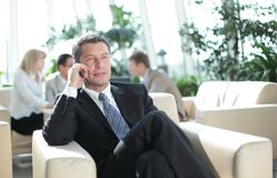 Happy young businessman using cell phone in hotel lobby Stock Photo