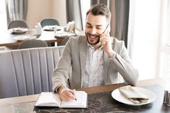Cheerful businessman working in cafe royalty free stock photography