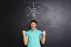 Happy confident young man celebrating success and having an idea. Over blackboard background Stock Photography