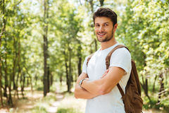 Happy confident young man standing with arms crossed in forest Stock Image