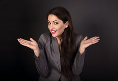 Happy confused business woman gesturing the hands in grey suit o. N dark background Stock Photos