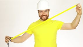 Happy construction engineer or architect using measure tape. Handsome happy construction engineer or architect in yellow tshirt and hard hat using measure tape stock footage