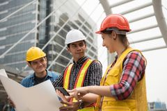 Construction team check plan from smartphone. Happy Construction team check project plan from smartphone in town while American female engineer point finger to Stock Photo