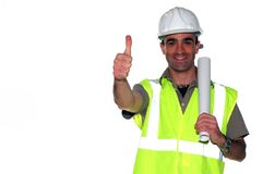 Happy construction worker. Happy spanish construction worker with an architectural plans showing his thumbs up Stock Photo