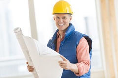 Happy Construction Worker Holding Blueprint At Site Royalty Free Stock Images