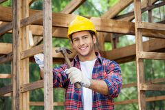 Happy Construction Worker Holding Hammer At Site Royalty Free Stock Photos