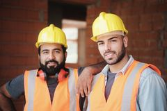 Happy Construction Workers Smiling At Camera In New Building. People working in construction site. Portrait of happy men at work in new house inside apartment royalty free stock photography
