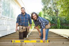 Happy Construction Workers With Spirit Level At Stock Photography