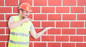Happy constructor pointing at his empty palm Stock Photo