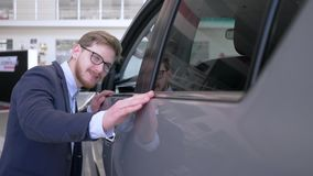 Happy consumer men into eyeglasses with pleasure stroking new automobile gently smiling at dealership. Close-up stock video