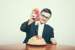 Happy consumerism. Concept. Happy businessman pouring ketchup on huge dish of pasta royalty free stock images