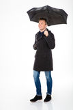 Happy content young male in coat  walking under umbrella Stock Photos