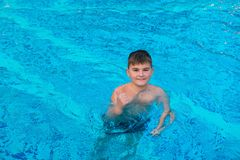 Happy contented boy bathing in the blue water of the pool. Copy space royalty free stock photo