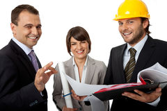 Happy contractor and investors. Happy three people wearing suits, one with helmet holding plans, isolated on white Stock Photography