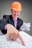 Happy contractor pointing to plans Royalty Free Stock Photography